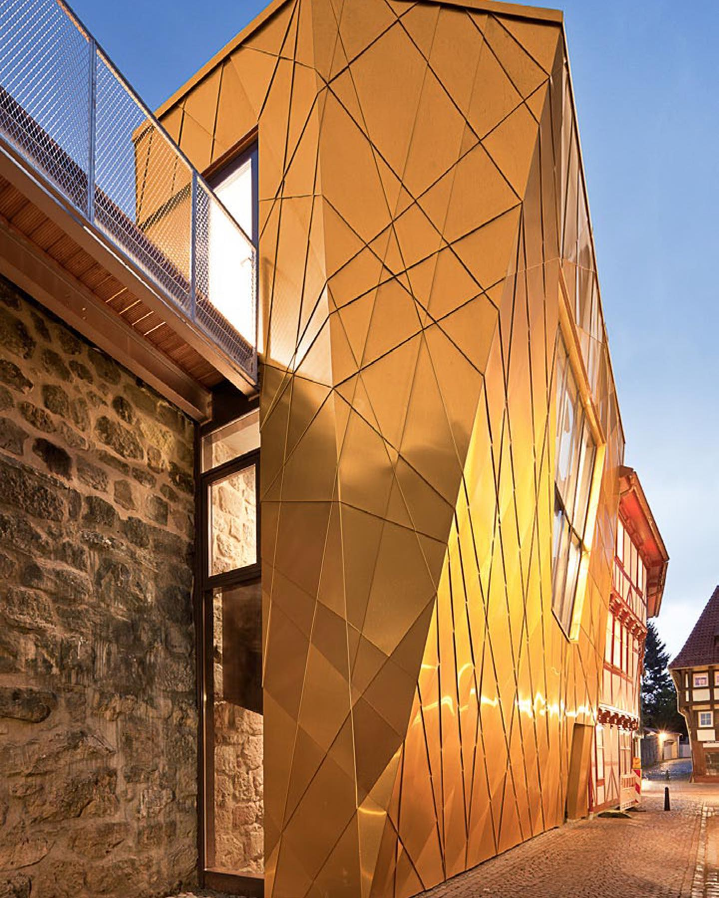 Museum at the town wall Built against the oldest section of the Duderstadt town wall, new exhibition space has been created in a prismatically folded structure. Inclined façade panels with shiny golden copper plate interpret the appeal of the historic building fabric in a modern architectural language. . . #architecturephotography #architecture #archidaily #architektur #archilovers #architecturedaily #architecture_hunter #berlinarchitecture #duderstadt